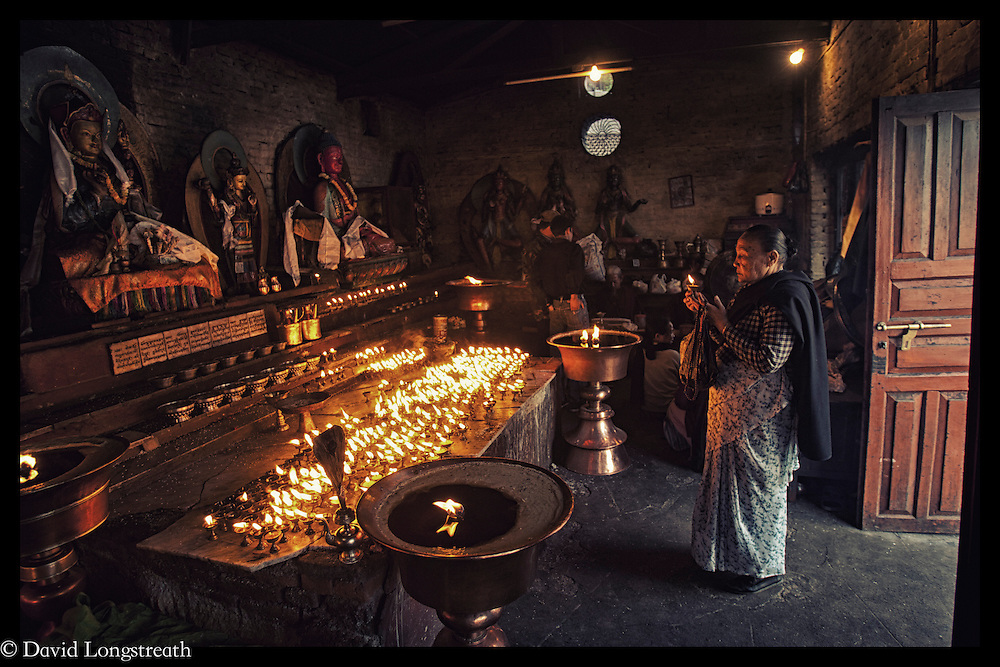 The faithful gather at one of the indoor shrine areas near the Bouddhanath, the oldest and largest Buddhist Shrine in Katmandu, Nepal.