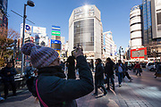 A Western woman tourist , wearing a wooly hat, takes a photo of Shibuya Crossing with a smart phone from Hachiko Square , Shibuya, Tokyo, Japan. Friday January 26th 2018