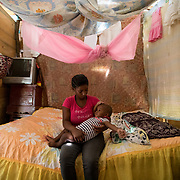 Elisa sits in on her bed with her baby daughter, Isabela* in the home they share with seven others in the Los Calzones in the San Juan De La Maguana Province community, that was flooded when Hurricane Irma hit the Dominican Republic, September 13, 2017. The river is the only source of water for mot of the community, and became so polluted that the government closed the pipe connection from the river to the community for seven days following the hurricane. The area is prone to diseases such as mosquitos, increasing cases of dengue, chikungunya, zika and others.