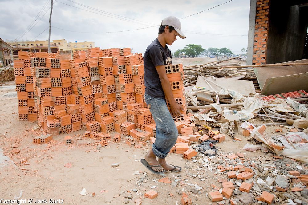 30 JUNE 2006 - PHNOM PENH, CAMBODIA: Workers at a high end housing development in Phnom Pehn, Cambodia, build new homes with bricks made at local brick factories. According the United Nations Food and Agricultural Organization, there are more than 70 brick factories in Phnom Penh and its environs. Environmentalists are concerned that the factories, most of which burn wood in their kilns, contribute to deforestation in Cambodia. They are encouraging factory owners to switch to burning rice husks, as brick kilns in neighboring Vietnam do. The brick factories are kept busy feeding Phnom Penh's nearly insatiable appetite for building materials as the city is in the midst of a building boom brought by on economic development and the need for new office complexes and tourist hotels.   Photo by Jack Kurtz / ZUMA Press