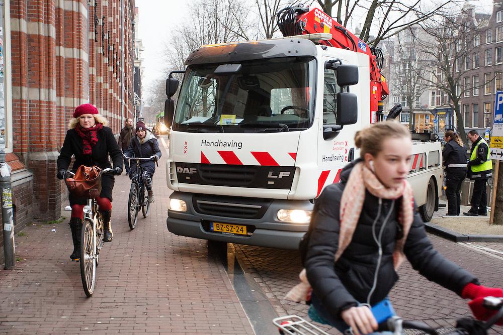 In Amsterdam moeten fietsers uitwijken voor een takelwagen van de dienst Handhaving van de gemeente Amsterdam die een fout geparkeerde auto weg wil slepen.<br /> <br /> In Amsterdam, cyclists must give way to a tow truck service of the Enforcement of the Amsterdam municipality that wants to tow an illegally parked car.