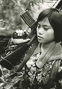 Young woman, member of Philippines revolutionary New People's Army, carries rifle