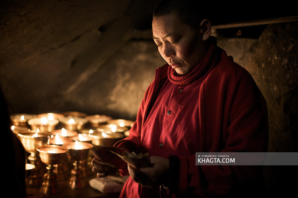 A nun counting donation money in the cave in Rewalsar village of Mandi, Himachal Pradesh. The cave is believed to be of Guru Pandmasambhava, also known as Guru Rinpoche who stayed here.