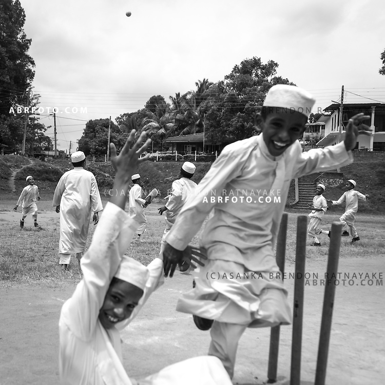 A group of Muslim school children celebrate after getting a batsmen out in a cricket match played at a local park in Arupola Kandy Sri Lanka