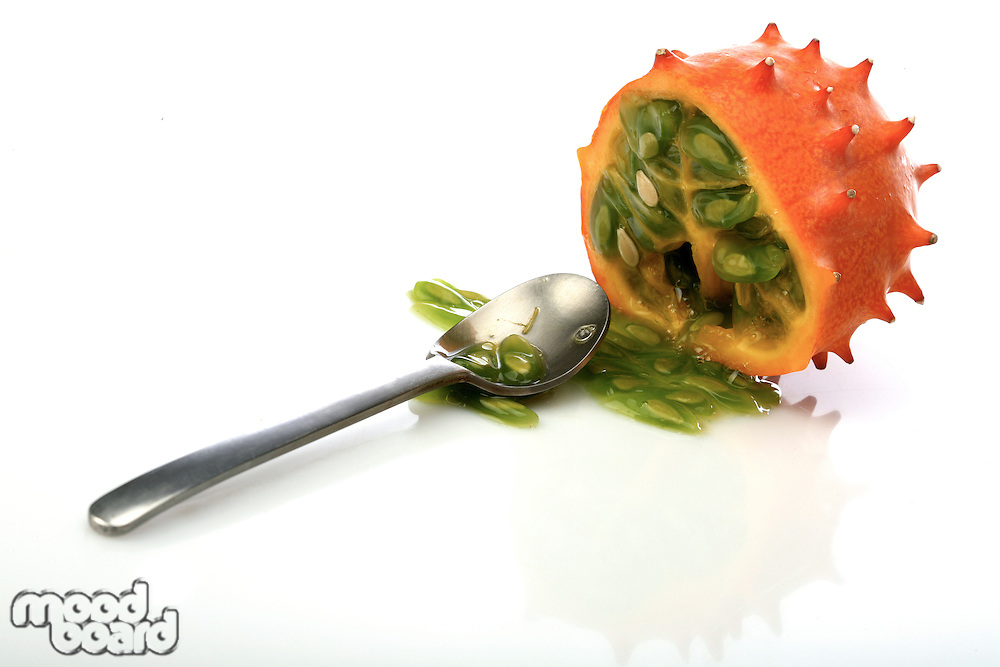 Kiwano and spoon on white background
