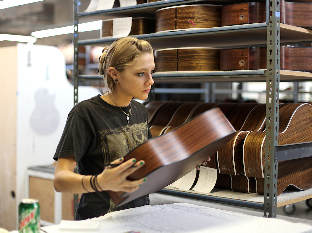A Taylor Guitar employee looks over a guitar body at the factory in San Diego.