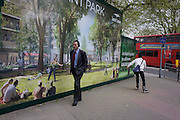 South Londoners walk past a regeneration project hoarding image at Elephant & Castle, London borough of Southwark.