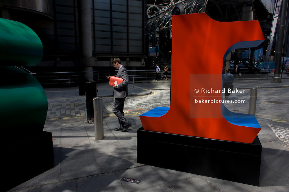 A city worker passes-by a large red number One, part of an art installation entitled 'One Through Zero (The Ten Numbers)' by American pop artist Robert Indiana (b 1928), in Lime Street, City of London, the capital's Square Mile, and its financial heart.