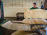 "15 DECEMBER 2014 - KLAENG, RAYONG, THAILAND: A worker rinses off rubber sheets at Supark, a rubber processing plant in Klaeng, Thailand. Thailand is the second leading rubber exporter in the world. In the last two years, the price paid to rubber farmers has plunged from approximately 190 Baht per kilo (about $6.10 US) to 45 Baht per kilo (about $1.20 US). It costs about 65 Baht per kilo to produce rubber ($2.05 US). Prices have plunged 5 percent since September, when rubber was about 52Baht per kilo. Some rubber farmers have taken jobs in the construction trade or in Bangkok to provide for their families during the slump. The Thai government recently announced a ""Rubber Fund"" to assist small farm owners but said prices won't rebound until production is cut and world demand for rubber picks up.      PHOTO BY JACK KURTZ"