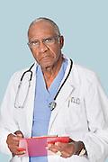 Portrait of a senior doctor holding clipboard over light blue background
