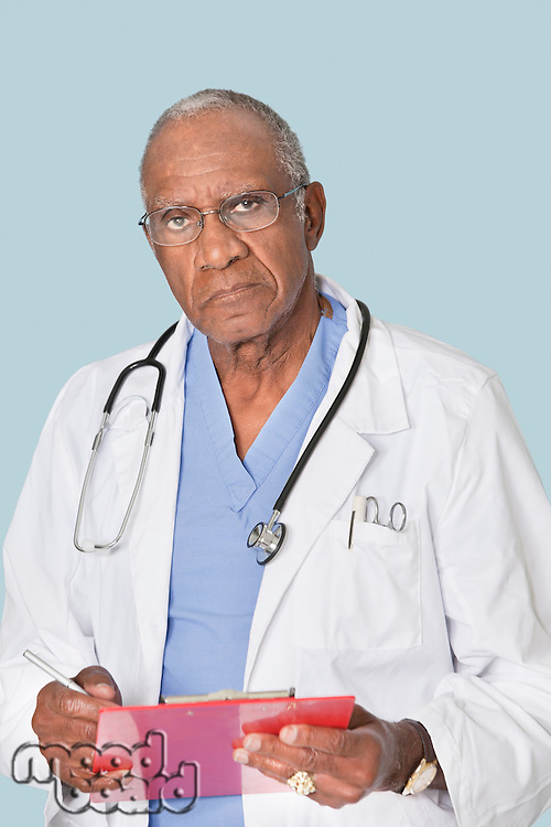 Portrait of a senior doctor holding clipboard over light blue background