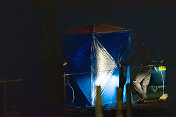 © Licensed to London News Pictures. 19/12/2019. London, UK. A police forensic tent is placed over a victim and vehicle in Scratchwood Park carpark after a man died of stab injuries. Police were called to Courtland Avenue, NW7, at 20:11GMT following a report of a fight in progress. Officers attended however no trace of any victim or suspects was found. At 20.27GMT, police were called by the London Ambulance Service to Barnet Bypass, near Scratchwood Park, to reports of a man, in his 20s, with stab injuries. Officers attended. The man was treated at the scene by paramedics before being taken to hospital. After a search of a car found at the scene, a man, in his 30s, was found inside a vehicle with stab wounds. Despite the efforts of emergency services, he was declared dead a short time later.. Photo credit: Peter Manning/LNP