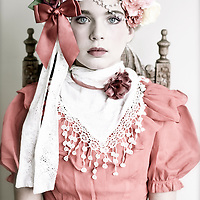 Adolescent female wearing period clothing with roses around her head looking at camera with serious expression
