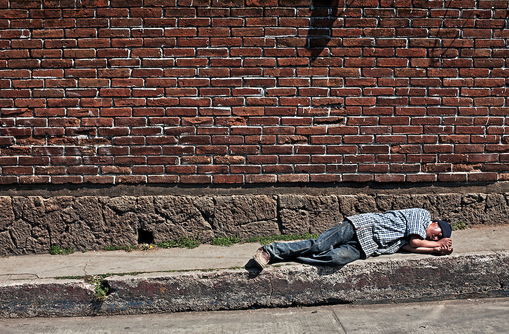 2012-01-26 San Juan Ostuncalco, Guatemala. Street scene in San Juan Ostuncalco, drunk man passed out on pavement next to street. Photo: Markus Marcetic