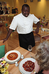 Chef talking to customer in Caribbean restaurant,