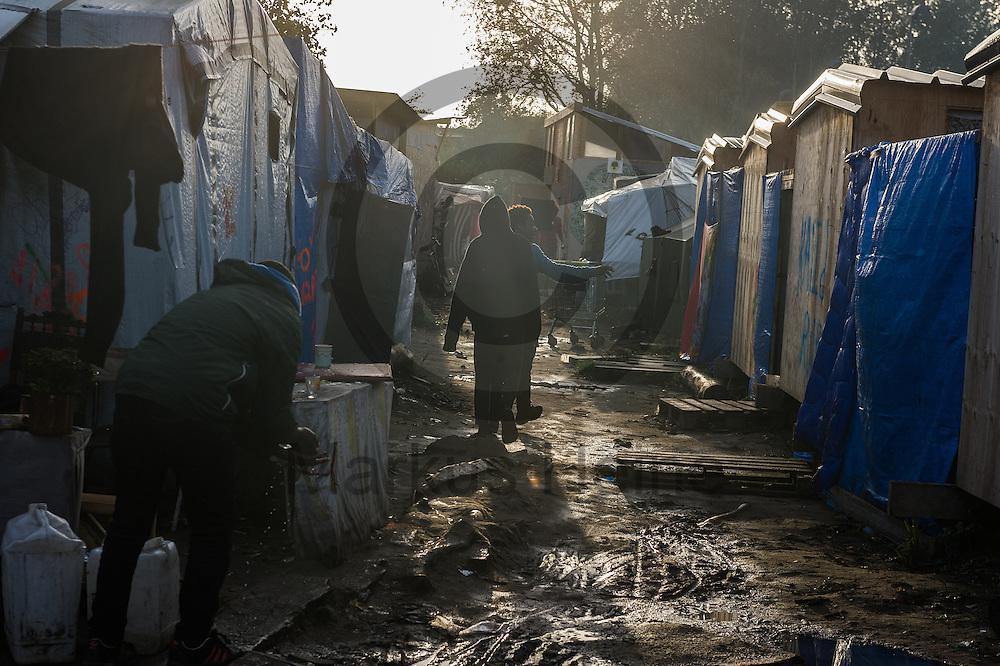 Calais, Frankreich - 17.10.2016<br /> Migranten laufen im Dschungel von Calais auf einem Weg zwischen den H&uuml;tten. Das Fluechtlingscamp an der Kueste zum Aermelkanal soll laut franz&ouml;sischer Regierung in den n&auml;chsten Tagen geraeumt werden. In dem Camp leben um die 1000 Fluechtlinge und warten auf die Moeglichkeit zur Weiterreise durch den Eurotunnel nach Gro&szlig;britannien. Photo: Foto: Markus Heine / heineimaging<br /> <br /> Calais, France - 2016/10/17Migrants<br />  walk in the Calais Jungle on a path between the huts. The refugee camp on the coast to the English Channel is to be cleared in the next few days, according to the French government. In the camp live around the 1000 refugees and wait for the possibility to travel further through the Eurotunnel to the UK. Photo: Foto: Markus Heine / heineimaging<br /> <br /> ------------------------------<br /> <br /> Ver&ouml;ffentlichung nur mit Fotografennennung, sowie gegen Honorar und Belegexemplar.<br /> <br /> Bankverbindung:<br /> IBAN: DE65660908000004437497<br /> BIC CODE: GENODE61BBB<br /> Badische Beamten Bank Karlsruhe<br /> <br /> USt-IdNr: DE291853306<br /> <br /> Please note:<br /> All rights reserved! Don't publish without copyright!<br /> <br /> Stand: 10.2016<br /> <br /> ------------------------------