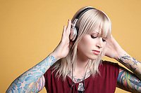 Young tattooed woman listening to music on headphones