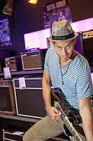 Portrait of young man playing electric guitar in music store