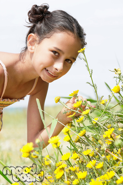 Smiling Pre-teen girl bending down smelling flower in field of flowers