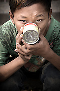 Glue-sniffing boy enjoying his moment. Glue-sniffing boy enjoying his moment. Glue sniffing is an activity to inhale the glue scent, mostly children from age 9-17 years old in street of Jakarta use it. The scent of the glue can make them relax and also help them to curb hunger.