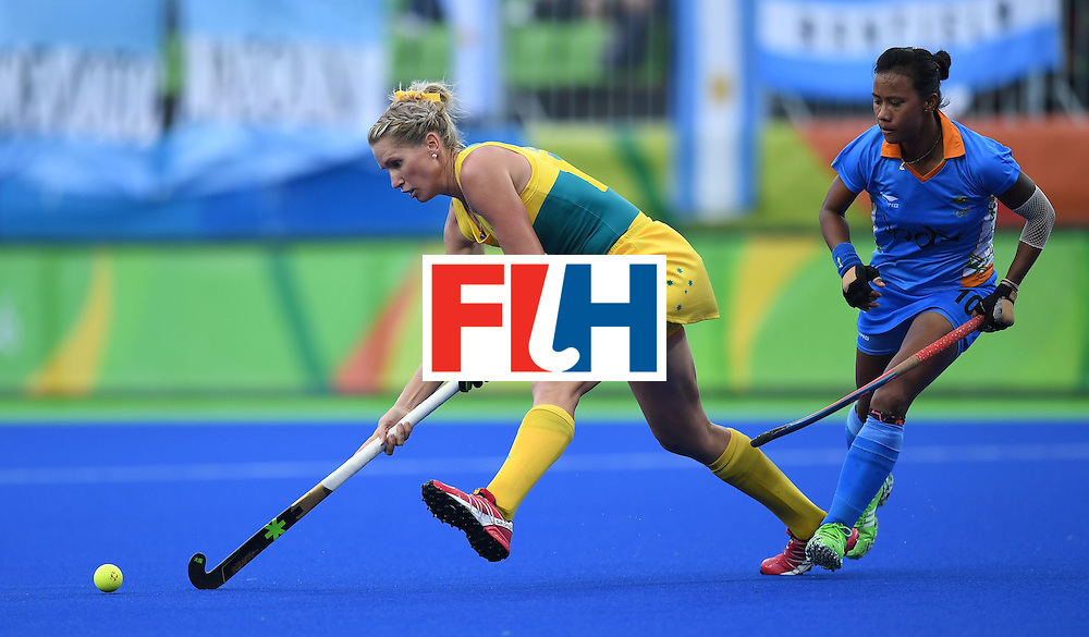 Australia's Jodie Kenny (L) hits the ball as India's Anuradha Thokchom looks on during the women's field hockey India vs Australia match of the Rio 2016 Olympics Games at the Olympic Hockey Centre in Rio de Janeiro on August, 10 2016. / AFP / MANAN VATSYAYANA        (Photo credit should read MANAN VATSYAYANA/AFP/Getty Images)