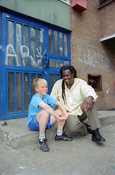 Boy and carer sitting on step outside entrance to block of flats; smiling,