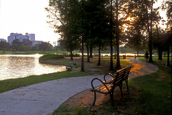 Stock photo of a shaded bench along a lakeside pathway in Hermann Park
