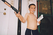 Young topless boy holding toy guns with a fake cigarette in mouth.