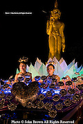 Two traditionally costumed Thai women ride on a passing float during the annual Loi Krathong Festival parade in Chiang Mai, Thailand.