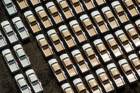 Aerial view of trucks parked before going to dealership. Aerial views of artistic patterns in the earth.