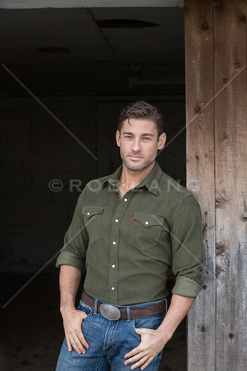 hot man leaning against a barn door