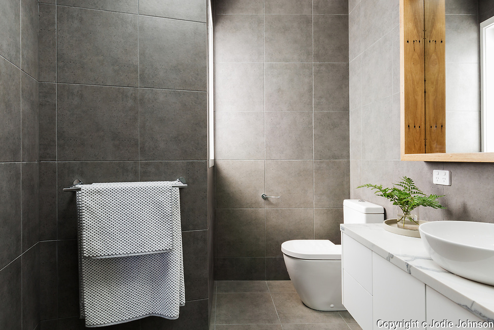Charcoal grey modern bathroom with marble benctop and wood mirror