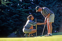 Woman teaches a man to golf on the putting green at Whistler Golf Course, Whistler, BC Canada.