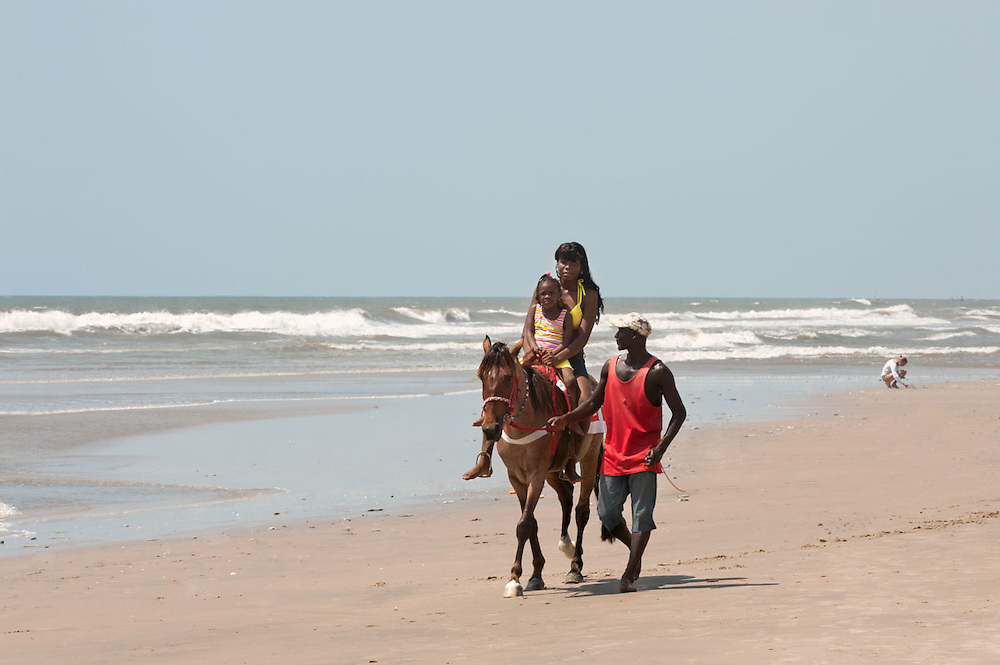 Family horse riding on Labadi beach, Accra, Ghana 2011