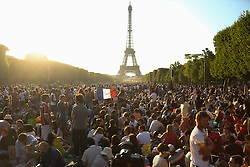 © Licensed to London News Pictures. 14/07/2015. Paris, FRANCE.  members of the public gather in the evening in front of the Eiffel Tower, waiting for a firework display, to celebrate Bastille Day on 14, July 2015. Photo credit: Jason Bryant/LNP