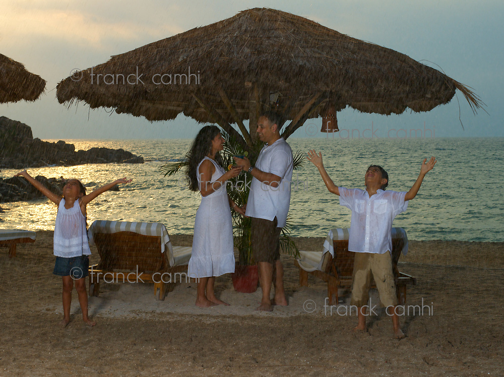 family enjoying their vacation in a resort under the  monsoon rain at the beach