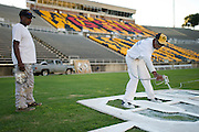 Louis Wright (right) begins painting the field at Eddie Robinson Stadium in advance of Grambling State Universities game against Texas Southern on October 26th with help from Terry Lee (left) in Grambling, Louisiana on October 23, 2013.  (Cooper Neill for The New York Times)