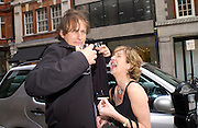 Lord Alexander Rufus-Isaacs sheltering Belinda Hadden's cigarette while she tries to light it. , Michelle Pearson Cooper private view, Cork St. 10 June 2003. © Copyright Photograph by Dafydd Jones 66 Stockwell Park Rd. London SW9 0DA Tel 020 7733 0108 www.dafjones.com
