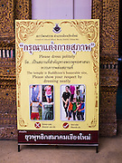 "03 APRIL 2015 - CHIANG MAI, CHIANG MAI, THAILAND:  A sign at the entrance to the ""wiharn"" (prayer hall) at Wat Ou Sai Kham in Chiang Mai asks visitors to dress and behave appropriately when they visit a Buddhist temple. Thailand has had problems with visitors who dress immodestly or behave improperly in temples, desecrating the holy places.     PHOTO BY JACK KURTZ"