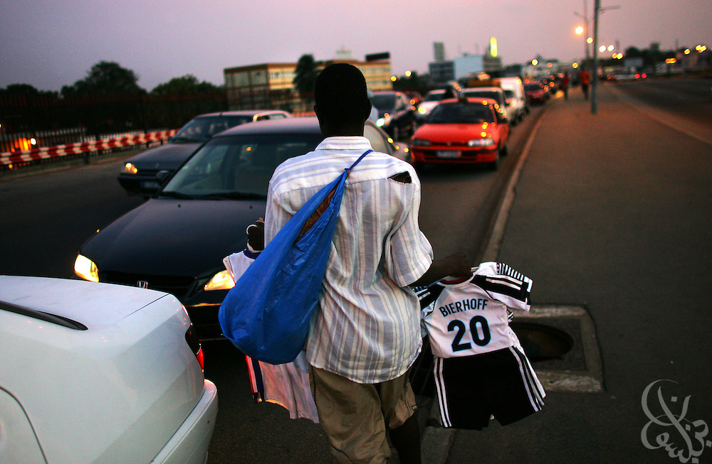 Street vendors sell football jerseys (including former German national player Bierhoff) during rush hour in the Plateau district of Abidjan, Ivory Coast February 17,2006. Football is an integral part of the social fabric that makes up Ivorian society.