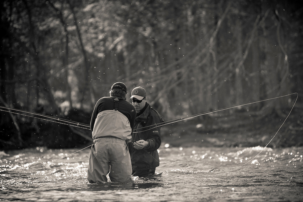male fly anglers exchangin flies while fishing for steelhead, Salmon River, New York