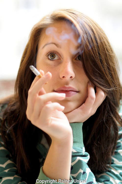 DEU , DEUTSCHLAND : Eine rauchende junge Frau mit Zigarette .  |DEU , GERMANY : A smoking young woman with cigarette|.   26.05.2010.   Copyright by : Rainer UNKEL , Tel.: (0)171/5457756