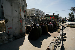 Men pray next to the rubble of a mosque destroyed by Israel in Gaza City.
