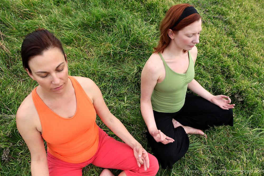 USA, California. Two mature healthy women share outdoor meditation.
