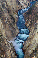 The deep blue of the Yellowstone River contrasts against the sulfur canyon walls