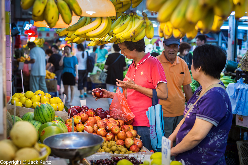 11 AUGUST 2013 - HONG KONG: A woman shops for fruit in a wet market in Kennedytown in Hong Kong. Hong Kong is one of the two Special Administrative Regions of the People's Republic of China, Macau is the other. It is situated on China's south coast and, enclosed by the Pearl River Delta and South China Sea, it is known for its skyline and deep natural harbour. Hong Kong is one of the most densely populated areas in the world, the  population is 93.6% ethnic Chinese and 6.4% from other groups. The Han Chinese majority originate mainly from the cities of Guangzhou and Taishan in the neighbouring Guangdong province.      PHOTO BY JACK KURTZ