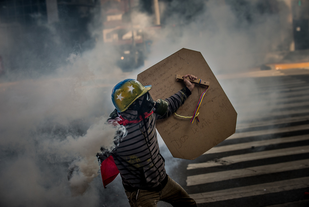 "CARACAS, VENEZUELA - MAY 20, 2017: An anti-government protester with a prayer that ends, ""God infront of me"" written on his homemade shield, throws a tear gas canister back at members of the National Police, who had previously shot it at a group of protesters during clashes in Caracas. The streets of Caracas and other cities across Venezuela have been filled with tens of thousands of demonstrators for nearly 100 days of massive protests, held since April 1st. Protesters are enraged at the government for becoming an increasingly repressive, authoritarian regime that has delayed elections, used armed government loyalist to threaten dissidents, called for the Constitution to be re-written to favor them, jailed and tortured protesters and members of the political opposition, and whose corruption and failed economic policy has caused the current economic crisis that has led to widespread food and medicine shortages across the country.  Independent local media report nearly 100 people have been killed during protests and protest-related riots and looting.  The government currently only officially reports 75 deaths.  Over 2,000 people have been injured, and over 3,000 protesters have been detained by authorities.  PHOTO: Meridith Kohut"