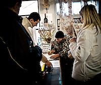 """Vincent Brunetti conclude una vendita di un suo quadro con dei clienti interessati alla sua arte prima dello """"Show"""" artistico all'interno della Galleria personale in Vincent City nei pressi di Guagnano in provincia di lecce. 29/03/2010 (PH Gabriele Spedicato)..VINCENT BRUNETTI.Affettuosamente identificato con l'appellativo """"LA LIBELLULA DEL SUD"""", Vincent Brunetti è oggi considerato uno dei personaggi più emblematici della vita artistica meridionale..Nato a Guagnano di Lecce il 3 dicembre 1950 e residente a Milano da oltre vent'anni dove per i meriti artistici (egli è infatti pittore e scultore) gli è stato conferito nel 1970 l'AMBROGINO D'ORO. Fu colpito in tenera età dal virus della poliomelite. Gli effetti devastanti della malattia a seguito di due delicati interventi al piede sinistro lo stavano portando ad una quasi totale immobilità..Comincia comunque a dipingere e consegue, con il massimo dei voti, il diploma alla Scuola d'arte di Lecce..Dopo essere stato a Torino, si trasferisce a soli venticinque anni a Milano dove riceve numerosi riconoscimenti ed entra in contatto con elementi di spicco della scena artistica milanese come Francesco Messina (sotto la cui guida frequenta l'Accademia di Brera); Giacomo Manzù che lo segue ed incoraggia nel corso della sua attività; Arnaldo Pomodoro che lo accoglie presso la sua Bottega..Sempre a Milano, egli collabora con l'attrice Paola Borboni ed il poeta Bruno Villar alla realizzazione di numerose attività culturali e di diversi programmi televisivi..Con il passare degli anni egli è sempre più debilitato dalla malattia..Grazie alla geniale scoperta di Mariano Orrico, ideatore """"Lamina Bior"""" secondo il quale, ogni genere di malattia può essere sconfitta con il proncipio dell'elettricità statica, Vincent Brunetti ha potuto recuperare in pieno la sua vitalità e gioia di vivere..Nella sua """"DANZA"""" propiziatoria è espresso in pieno il bisogno di LIBERTA' che è nascosto nel cuore di ogni uomo e nel suo """"VOLO"""" il desiderio di libera"""