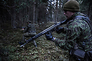Young recruits training in the forests in Central Lithuania. Over the weekend, a great number of reservists participate in the training session on the ground only to resume their ordinary lives during the rest of the week.