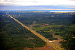 CANADA ALBERTA FORT MCMURRAY 28SEP09 - Aerial view of a large clearcut for power lines running through the the Boreal forest north of Fort McMurray, northern Alberta, Canada...The tar sand deposits lie under 141,000 square kilometres of sparsely populated boreal forest and muskeg and contain about 1.7 trillion barrels of bitumen in-place, comparable in magnitude to the world's total proven reserves of conventional petroleum. Current projections state that production will  grow from 1.2 million barrels per day (190,000 m³/d) in 2008 to 3.3 million barrels per day (520,000 m³/d) in 2020 which would place Canada among the four or five largest oil-producing countries in the world...The industry has brought wealth and an economic boom to the region but also created an environmental disaster downstream from the Athabasca river, polluting the lakes where water and fish are contaminated. The native Indian tribes of the Mikisew, Cree, Dene and other smaller First Nations are seeing their natural habitat destroyed and are largely powerless to stop or slow down the rapid expansion of the oil sands development, Canada's number one economic driver...jre/Photo by Jiri Rezac / GREENPEACE..© Jiri Rezac 2009